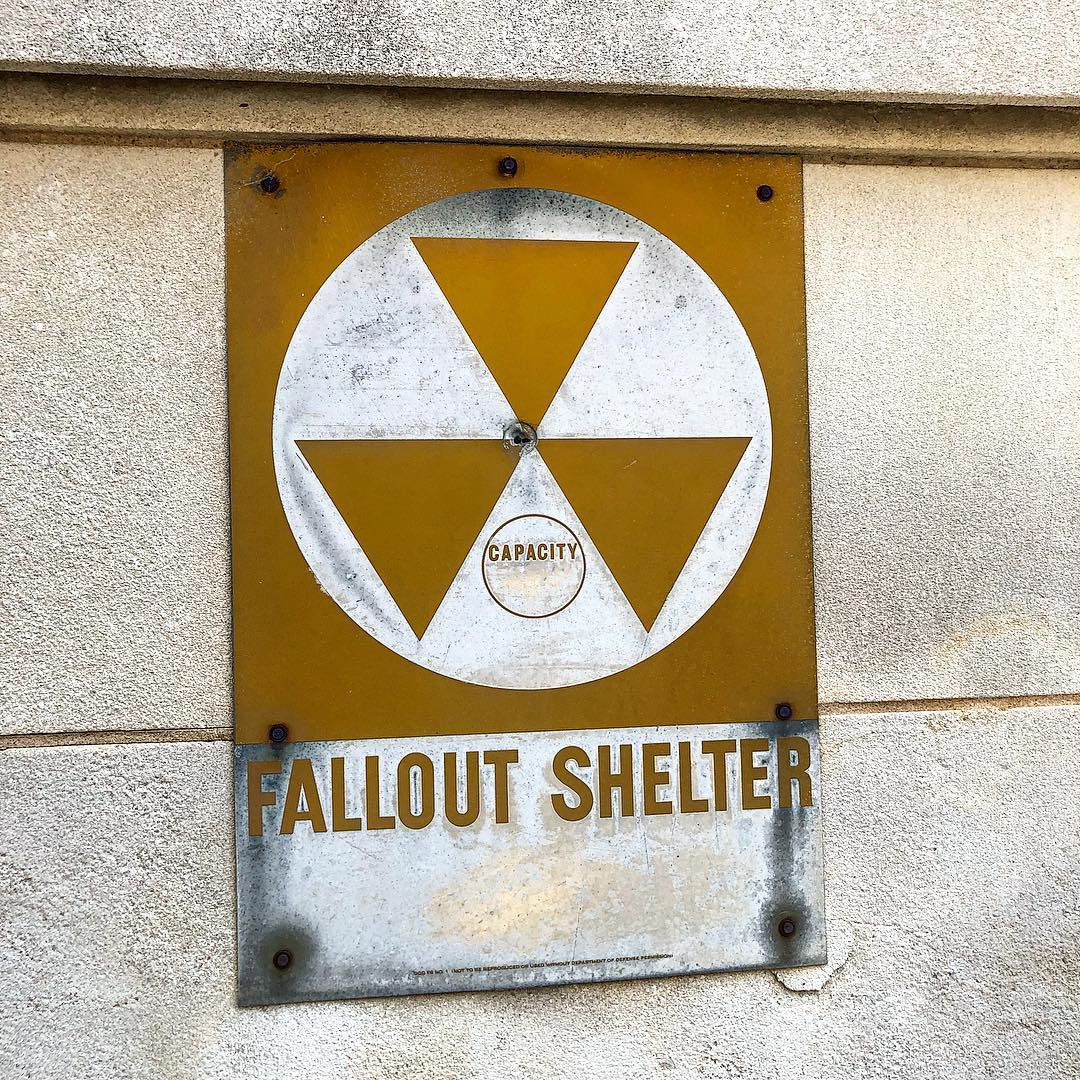 During the Cold War, many countries built fallout shelters. Plans were made, however, to use existing buildings with sturdy below-ground-level basements as makeshift fallout shelters. These buildings were placarded with the orange-yellow and black trefoil sign designed by United States Army Corps of Engineers in 1961. The program was abandoned in the 1970s