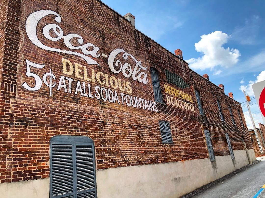 "Coca-Cola advertising over a Pepsi-Cola advertisement. ""Refreshing Healthful"" was a Pepsi slogan"