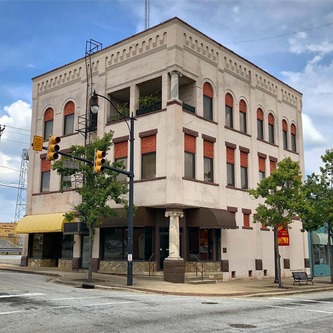 The Settlemyer Building was constructed in 1903. This 3-story brick building was the home of Cherokee Savings Bank for many years. The building features a corner entrance with a marble Iconic column. Pilasters divide the upper facade and at the roofline is a corralled brick cornice. Windows on the third story have rounded arches; a recessed balcony is also located on the third floor