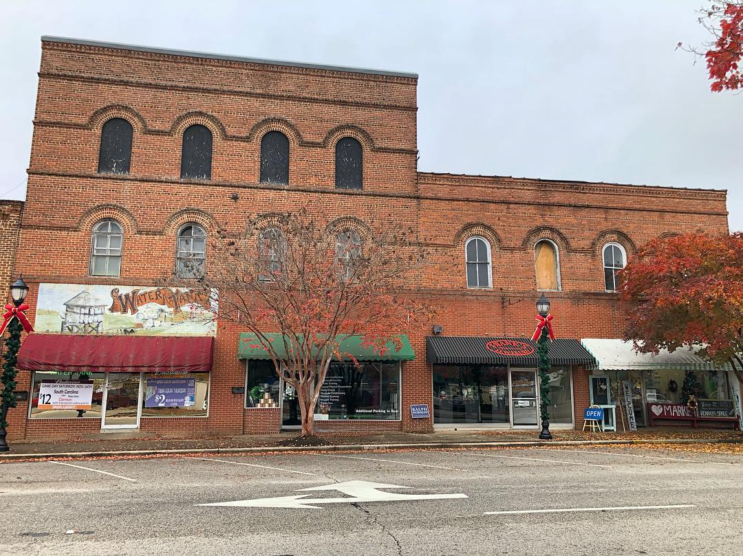 These brick buildings were erected in 1886 by John J. Smith as a 1 story commercial building and expanded to 2 stories in 1906.  The building on the left was the home of Smith's store. The second floor was an opera house and Town Hall, then the 3rd floor as a Masonic Hall. The right building was used as Clover Drug Store, the Bank of Clover, and legal and medical offices on the second floor